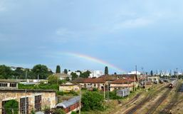 Sommarcityscape: en regnbåge över en järnväg bussgarage med många stänger, vagnar, drev royaltyfria foton