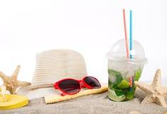 Sommarcoctail med strandtillbehör i sanden royaltyfri bild