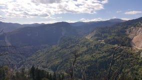 Sommardag i bergen med mörk himmel Arkivfoton