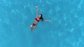 Sommardagen i pöl, simmar den flyg- sikten av den attraktiva flickan i baddräkt i blått vatten lager videofilmer