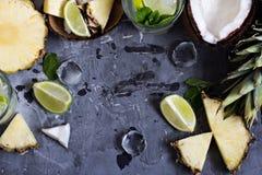 Sommardrink, coctail, te, tropiska frukter, ananas, kokosnöt, limefrukt, sommarbakgrund arkivbilder
