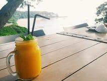 Sommardrink: En glass krus av mangofruktsaftsmoothien är på trätabellen med seaview Royaltyfri Foto