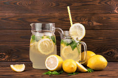 Sommardrinklemonad med mogna citroner, mintkaramellen och is på en mörk trätabell Lemonad med nya citroner och den gröna mintkara Royaltyfria Foton