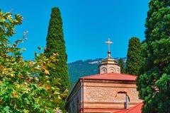 SOMMAREN landskap Liten kristen tempel i bakgrund av berg och träd royaltyfria bilder