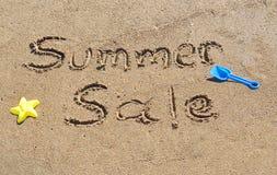 Sommarförsäljning som är skriftlig i sanden royaltyfria foton