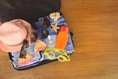 Sommarfamiljsaker och tillbehör i resväska royaltyfri fotografi