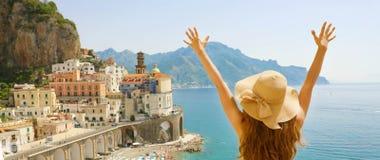 Sommarferie i Italien Panorama- tillbaka sikt av den unga kvinnan med sugrörhatten med lyftta armar som ser den Atrani byn, Amalf royaltyfri foto