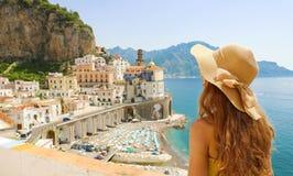 Sommarferie i Italien Tillbaka sikt av den unga kvinnan med sugrörhatten och den gula klänningen med den Atrani byn på bakgrunden royaltyfri bild