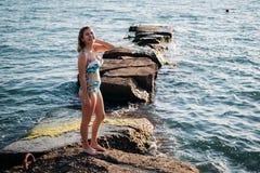 Sommarferier, lopp, folk och semester begrepp - lycklig ung kvinna i bikini över bakgrund för blå himmel och havspå solnedgången arkivbilder