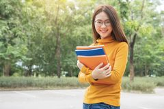 Sommarferier, utbildning, universitetsområde och tonårs- begrepp - le den kvinnliga studenten i svart glasögon med mappar och gru arkivfoto