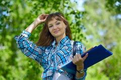 Sommarferier, utbildning, universitetsområde och tonårs- begrepp - le den kvinnliga studenten med mappar royaltyfria bilder