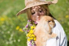 Sommarflicka med kaninen i naturen Fotografering för Bildbyråer
