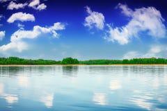 Sommarflodlandskap i molnig dag Arkivfoto