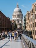 Sommarfolkmassor svaller över milleniumbron in mot St Paul arkivbilder