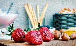 Sommarfrukost med jordgubben, muttrar, pastery och en yoghurt Royaltyfri Fotografi