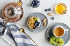 Sommarfrukosten med granola, blåbäret och druvan med mjölkar arkivbilder