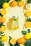 Sommarfruktvatten med citronen, apelsinen, mintkaramellen och is i murarekrus på guling Tropiskt begrepp royaltyfri bild