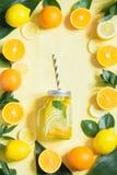 Sommarfruktvatten med citronen, apelsinen, mintkaramellen och is i murarekrus på guling Tropiskt begrepp arkivbilder