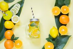 Sommarfruktvatten med citronen, apelsinen, mintkaramellen och is i murarekrus på guling Tropiskt begrepp ovanför sikt royaltyfria bilder
