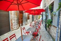 Sommargatakafé med röda paraplyer och stolar royaltyfria foton