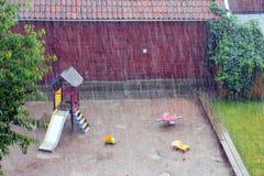 Sommarhällregn i staden En liten borggård med en sandlådaglidbana och leksaker arkivfoto