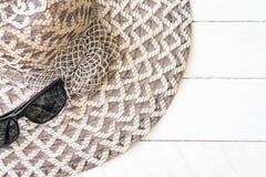 Sommarhatt med solglasögon på vitt trä royaltyfri bild