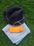 Sommarhatt, strandhandduk och sunscreenlotion på gräset Arkivfoton