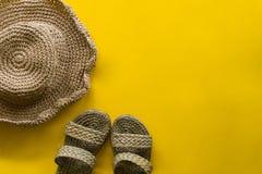 Sommarhattv?v och sandalv?v med gul bakgrund royaltyfri bild
