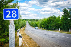 Sommarhuvudväg med det blåa tecknet och molnen Arkivbilder