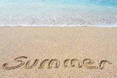 Sommarinskriften på en tropisk sandig strand med blått ser på en bakgrund royaltyfri bild