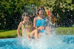 Sommarkondition, ungar i simbassäng har gyckel som ler flickor, plaskar i vatten arkivbild