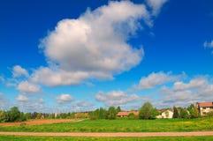 Sommarlandskap av blå himmel, vitmoln och det gröna fältet Arkivfoto