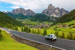 Sommarlandskap av Dolomiti med byar på den gräs- backen av ojämna berg & bilar som reser på en huvudväg arkivbild