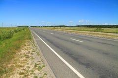 Sommarlandskap för väg och för blå himmel Arkivfoto