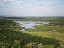 Sommarlandskap med den lilla floden i avståndet Arkivfoto