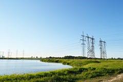 Sommarlandskap med elektricitetspyloner royaltyfri fotografi