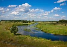 Sommarlandskap med en flod på bakgrundshimmel Arkivfoton