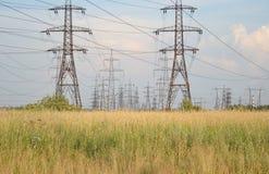 Sommarlandskap med kraftledningen Arkivbild