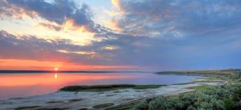 Sommarlandskap på bankerna av sjön på solnedgången royaltyfria bilder