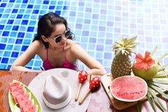 Sommarlivsstilsemester, flicka som kopplar av i den blåa pölen fotografering för bildbyråer