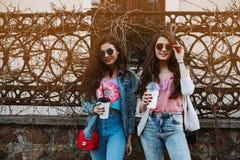 Sommarlivsstilstående av två stilfulla kvinnor för hipster med den sexiga kroppen för passform, den bärande grov bomullstvilldräk Arkivfoto