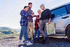 Sommarloppbegrepp Lyckliga vänner som använder pappersöversikten nära den hyrda bilen i natur Lyckliga handelsresande i berg på h royaltyfri foto