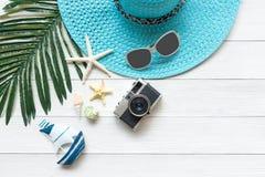 Sommarmode, kamera, sjöstjärna, sunblock, solexponeringsglas, hatt Resa och semestrar i ferien, wood vit bakgrund royaltyfri foto