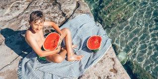Sommarplesuares: pojke som ?r klar att ?ta den stora vattenmelon, n?r att ha simmat i havet royaltyfri bild