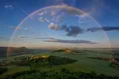 Sommarregnbåge över tjeckiska bohemiska Skotska högländernakullar, Tjeckien regnig solnedgång royaltyfria bilder