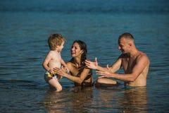 Sommarsemester av den lyckliga familjen sommar vilar av den lyckliga familjen i havsvatten Arkivbilder
