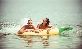 Sommarsemester och lopp till havet Koppla ihop förälskad sunbath på stranden på luftmadrassen Uppblåsbar madrass för ananas royaltyfria foton