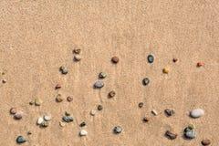 Sommarsikt av små runda kiselstenar på den soliga stranden royaltyfria bilder