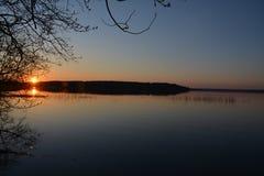 Sommarsolnedgång över en stor sjö arkivfoton