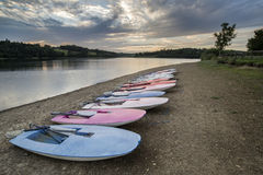 Sommarsolnedgång över sjön i landskap med fritidfartyg och equi Royaltyfria Bilder